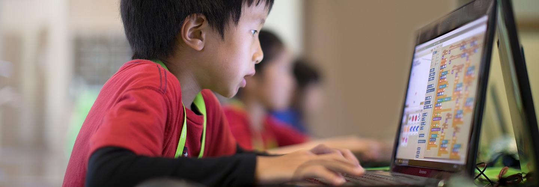 Ребенок поглощен программирование на языке Scratch